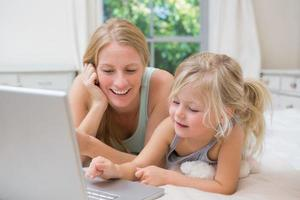 Cute little girl and mother on bed using laptop photo