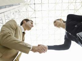 empresários confiantes apertando as mãos contra o teto