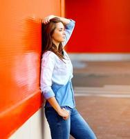 Beautiful woman posing near bright colorful wall