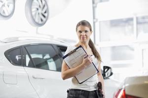 Retrato de seguro mecánico femenino con portapapeles en taller de coches foto