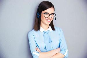 Feliz empresaria con auriculares y brazos cruzados foto