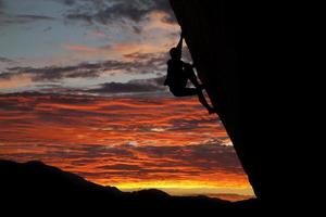 escalador con impresionante atardecer como telón de fondo foto