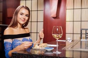 mujer en un restaurante muestra el pulgar hacia arriba foto