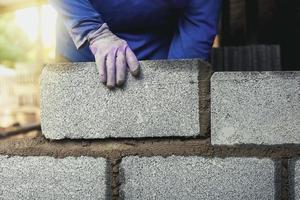 trabalhador da construção civil construindo um muro