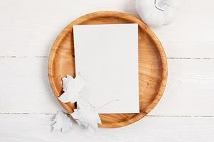 plato de madera con hoja de papel blanco foto