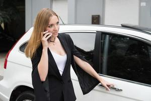 Woman talking on the phone opening car door