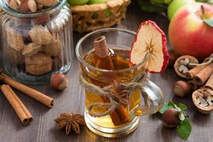 apple cider with spices in glass mug, top view