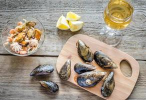 Mussels with a glass of wine on the wooden table
