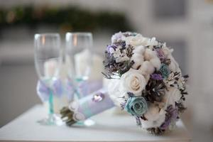 A wedding bouquet with white, purple, and blue flowers