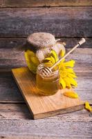 Jar of honey with sunflowers and spoon