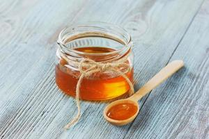 Honey in a wooden spoon and jar