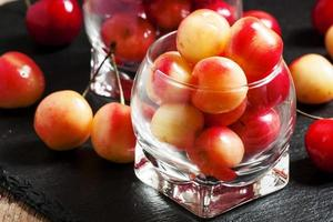 Red and yellow ripe cherries in a glass bowl