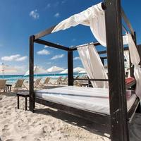 Luxury wooden lounge beds on caribbean beach photo