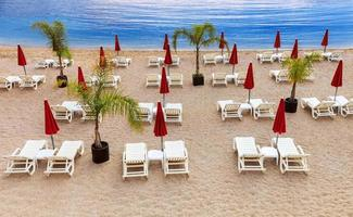 Empty beach with white sunbeds and red umbrellas