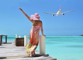 achteraanzicht van meisje in slappe strandhoed staande op pier