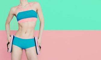 Fitness girl in fashionable sports swimsuit on vanilla backgroun photo