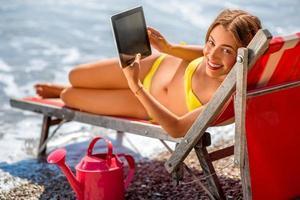 mulher usando tablet digital na espreguiçadeira