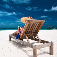 mujer joven, con, teléfono móvil, en la playa