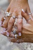 Mujer lavando sus joyas con las manos cubiertas de agua
