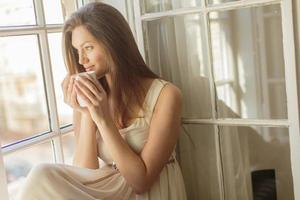 Pretty young woman by the window
