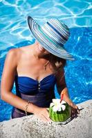 Woman in hat relaxing at the poolside with exotic cocktail