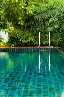 Grab bars ladder in the blue swimming pool photo