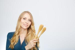 young woman holding a wooden spoon, isolated