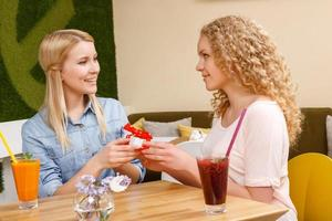 Two girls giving each other presents in cafe photo
