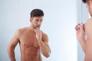 Young man brushing teeth photo