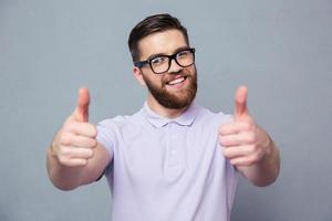 Casual man in glasses showing thumb up photo