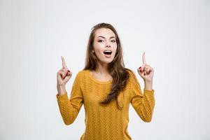 Happy woman pointing fingers up photo