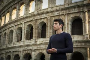 Handsome young man in Rome standing, front of the Colosseum
