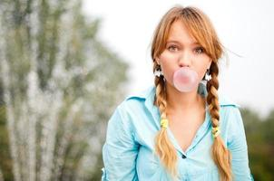 Young redheaded student in pigtail braids blows bubblegum photo