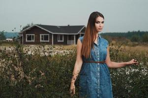 cute countryside lady standing in tall grass against ranch house photo