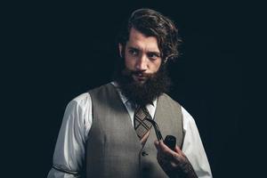 homem com barbicha comprida segurando um cachimbo de cigarro