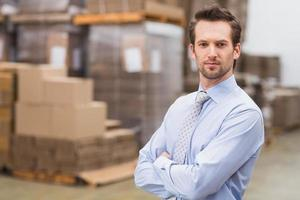 Serious manager with arms crossed in warehouse