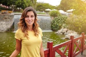 mulher bonita sorrindo em pé perto do lago