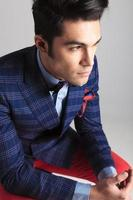 young fashion man sitting while looking away.