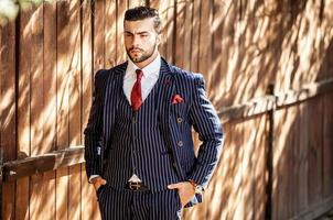 Man against wooden fence In stylish suit.