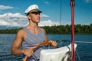 Young man sailor at the helm of yacht