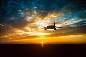 Airplane in the sky at sunset photo