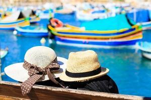 Dos sombreros con barcos tradicionales malteses en el fondo