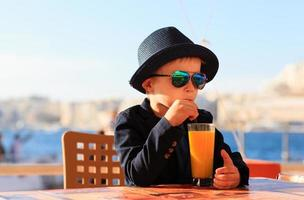 little boy drinking juice in outdoor cafe at the sea