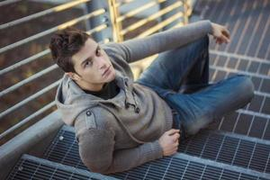 Handsome young man, sitting and leaning on metal grid stairs