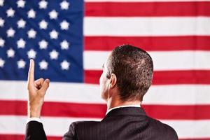 Retrovisor del hombre traje apuntando hacia la bandera estadounidense