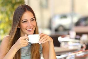Mujer pensativa pensando en la terraza de una cafetería foto