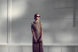 Street fashion concept - pretty elegant woman in leopard dress photo