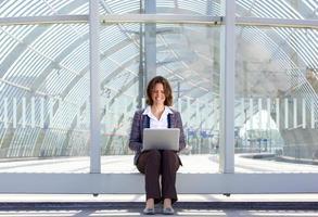 mujer de negocios, sentado, afuera, y, mirar la computadora portátil