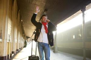 Young man waving hand at train station