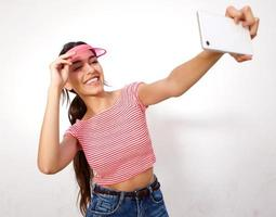 Mujer joven riendo y tomando selfie con teléfono móvil